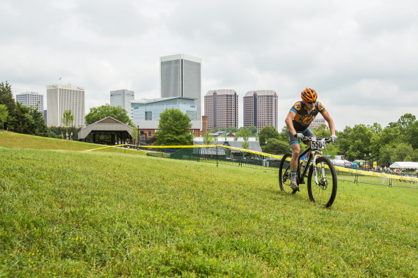 A mountain biker makes their way across a field with the city skyline